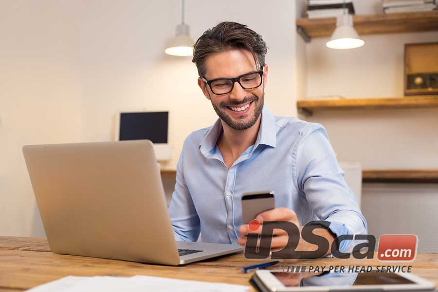 Young man wearing glasses, reading reviews of pay per head companies